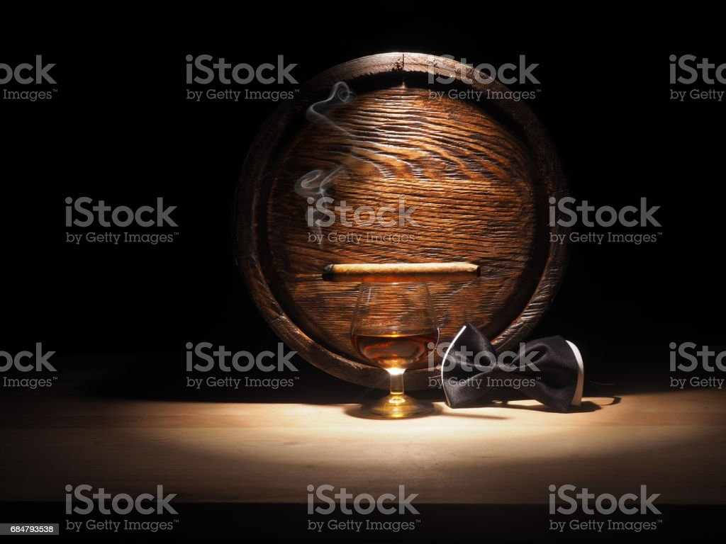 Glass of brandy, Cigar and old oak barrel stock photo