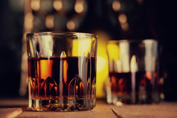 glas brandy auf dem holztisch - mahagoni braun stock-fotos und bilder