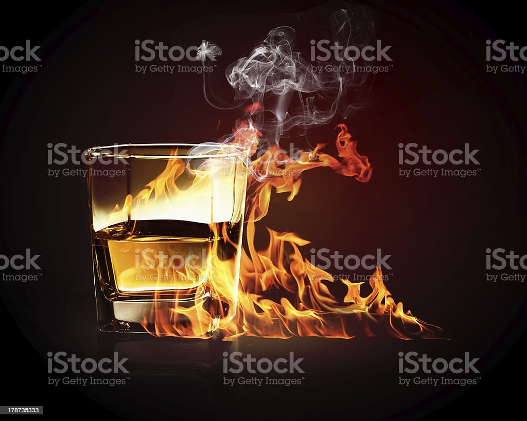 Glass of burning yellow absinthe royalty-free stock photo