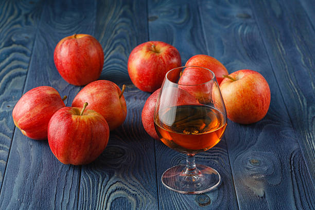 glass of Calvados Brandy and red apples glass of Calvados Brandy and red apples calvados stock pictures, royalty-free photos & images