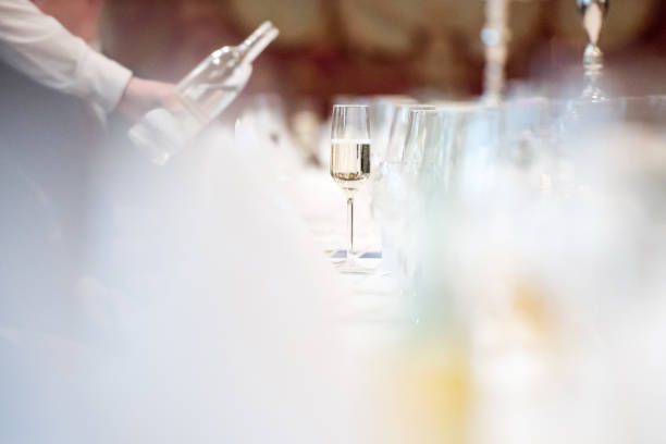 glass of champagne at table Germany: A glass of champagne at a long table. epernay stock pictures, royalty-free photos & images