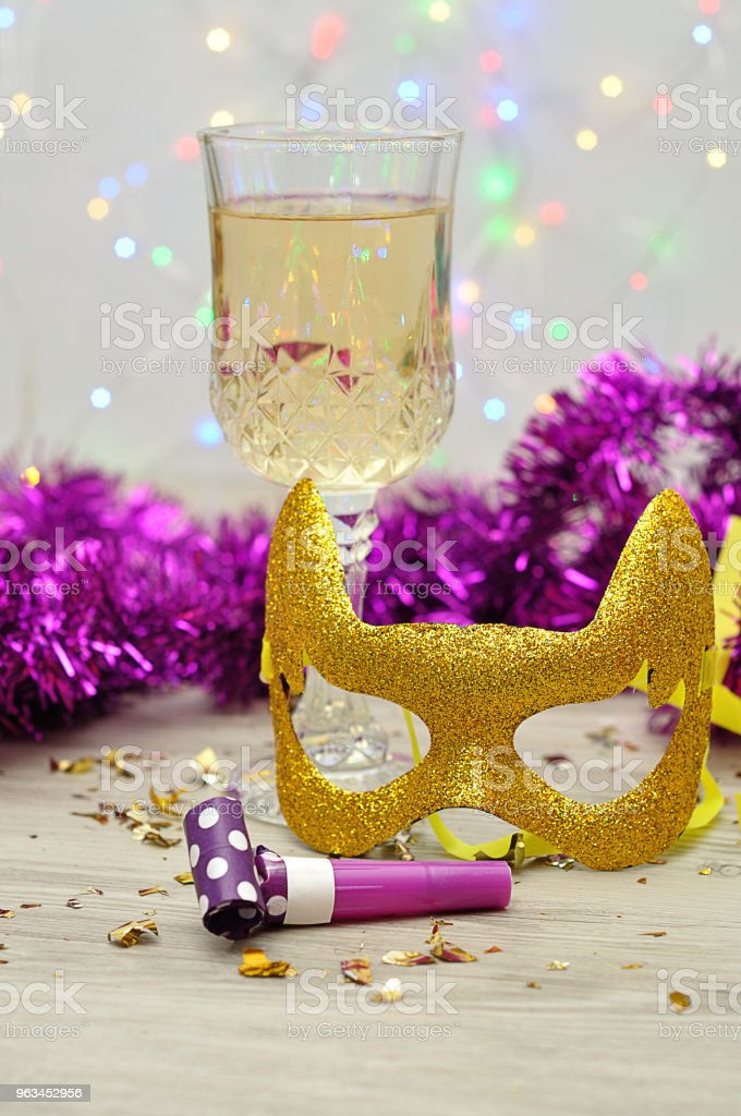 A glass of champagne displayed with a mask, party blower and tinsel - Zbiór zdjęć royalty-free (Alkohol - napój)