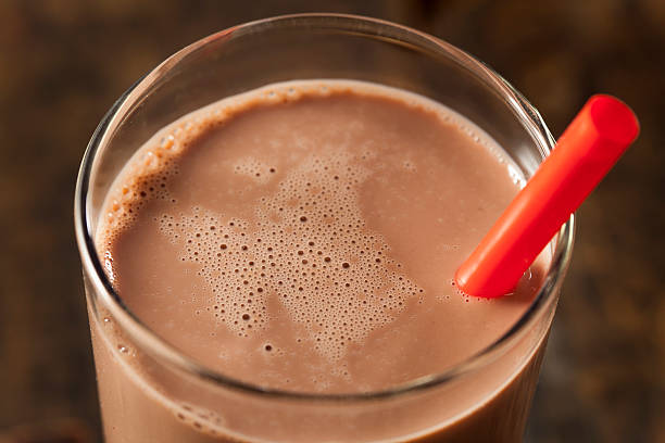 A glass of chocolate milk with a red straw sticking out Refreshing Delicious Chocolate Milk with Real Cocoa chocolate milk stock pictures, royalty-free photos & images