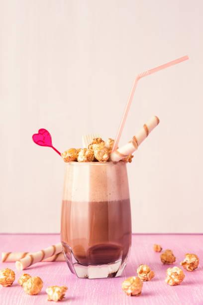 glas schokolade milchshake mit karamell popcorn. - kaffee protein shakes stock-fotos und bilder