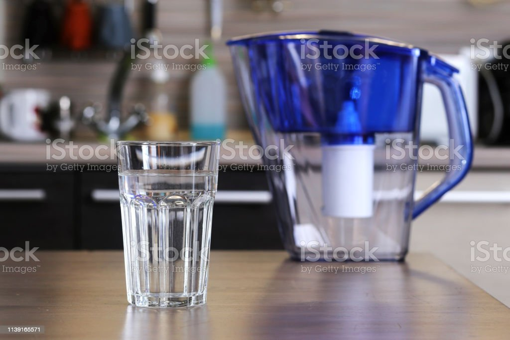 Glass of clean water and filter for cleaning drinking water on the...