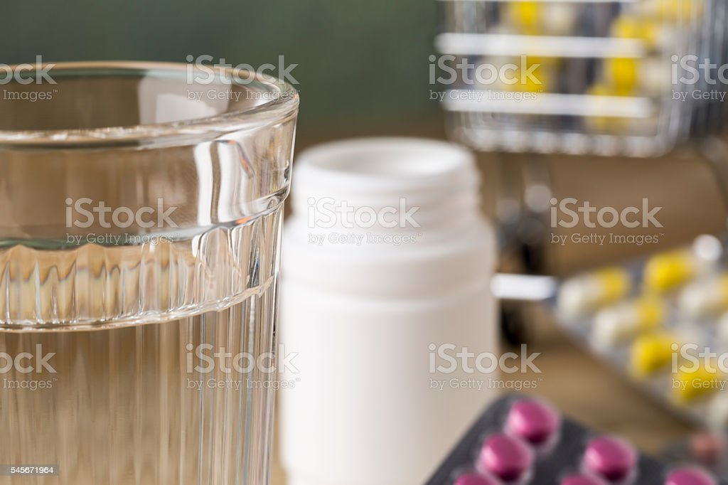 Glass of clean water and pill blister packs stock photo