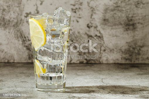 Glass of clear water with ice and lemon on a gray background. Close-up. Copy space.