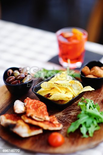 istock Glass of cocktail (sparkling wine with Aperol) and appetizer platter 696746770