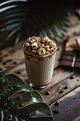 Glass of coffee and caramel popcorn, coffee beans and chocolate. Tropical leaves