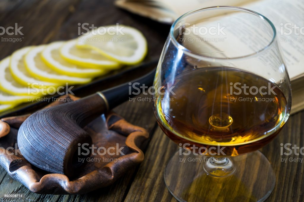 A glass of cognac, a pipe in the ashtray, sliced lemon on a glass plate and an old book on textured oak table. stock photo