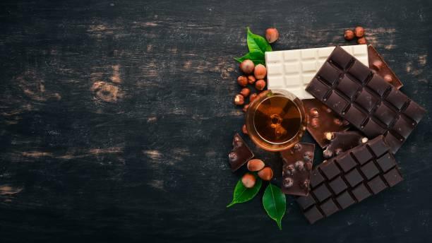 ein glas cognac, brandy, whiskey und eine reihe von schokolade mit keksen und süßigkeiten. auf einem schwarzen hintergrund aus holz. platz für text zu kopieren. - schokolikör stock-fotos und bilder