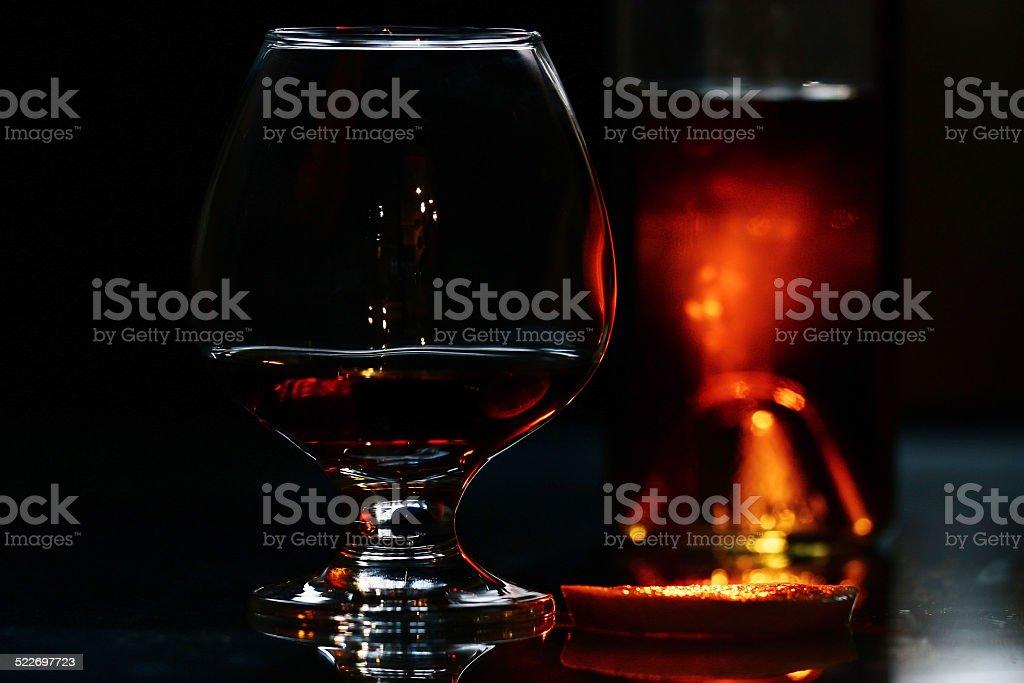 glass of cognac on black background stock photo