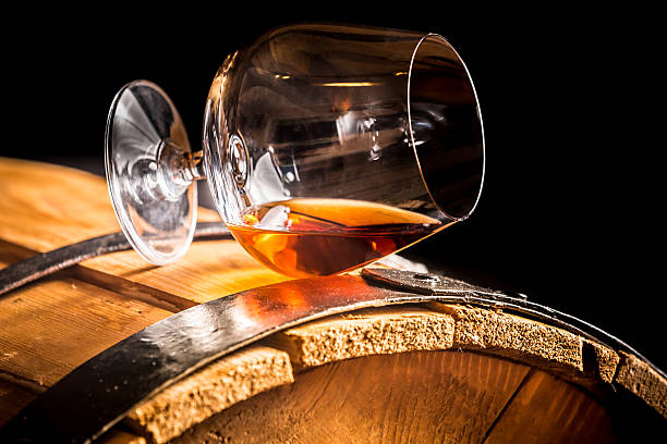 glass of cognac on the old wooden barrel - 干邑 白蘭地 個照片及圖片檔