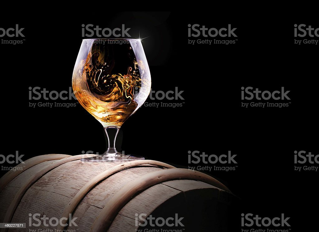 Glass of cognac or brandy on a barrel stock photo