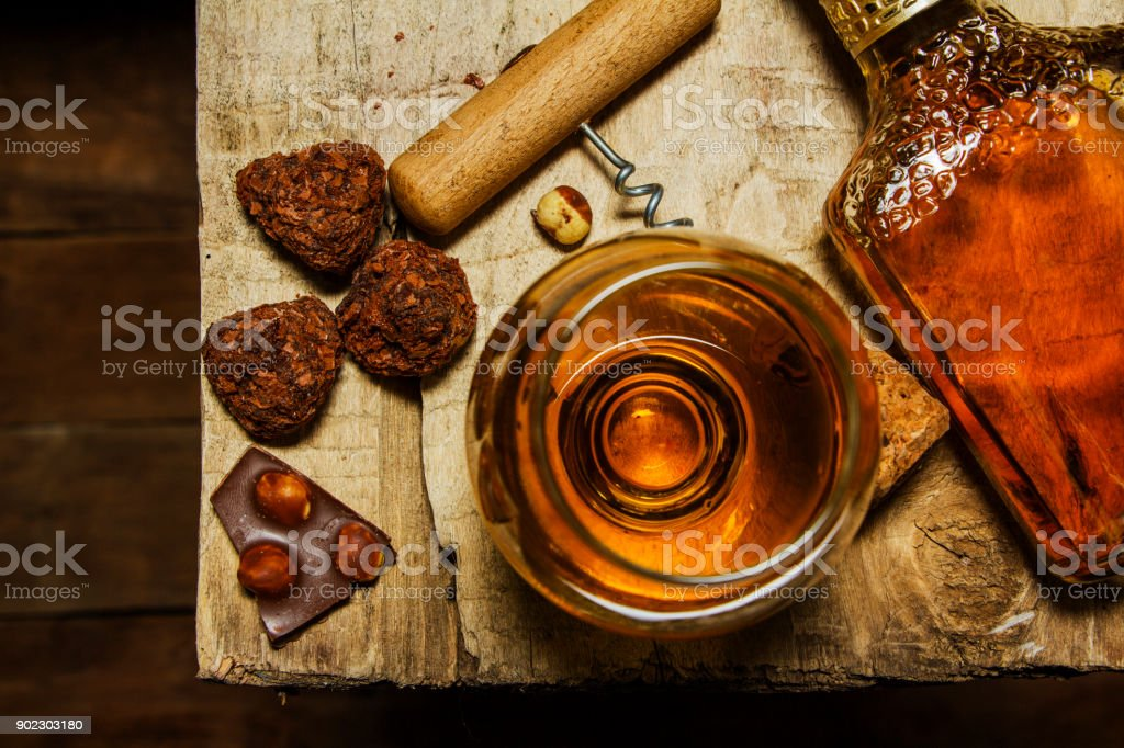 A glass of cognac or whiskey on a rustic table with chocolate and truffles. stock photo