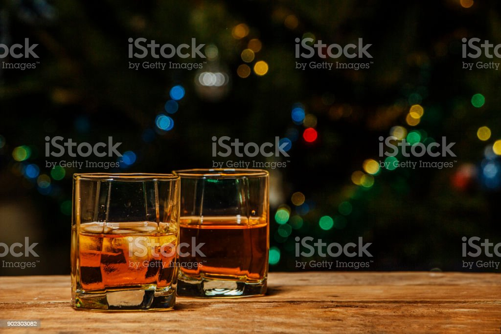 A glass of cognac or whiskey on a village table in the background of lights. stock photo