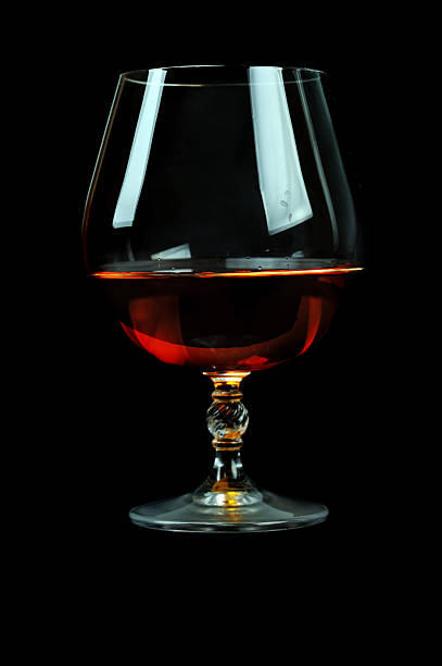 glass of cognac elegant  glass of cognac on table. black background calvados stock pictures, royalty-free photos & images