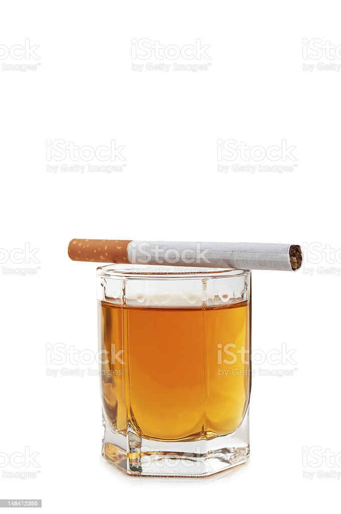Glass of cognac with a cigarette on the top royalty-free stock photo