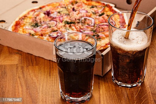 Glass of coke and pizza on the table