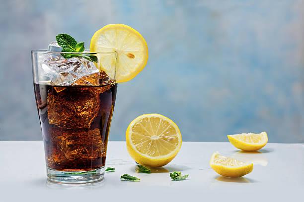 glas von cola mit eiswürfeln und zitrone scheiben - alkoholfreies getränk stock-fotos und bilder