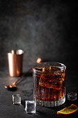 Glass of cold cola with ice cubes on dark background