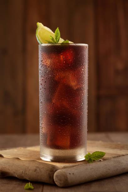 glas cola mit eis. - tropfenblatt tisch stock-fotos und bilder