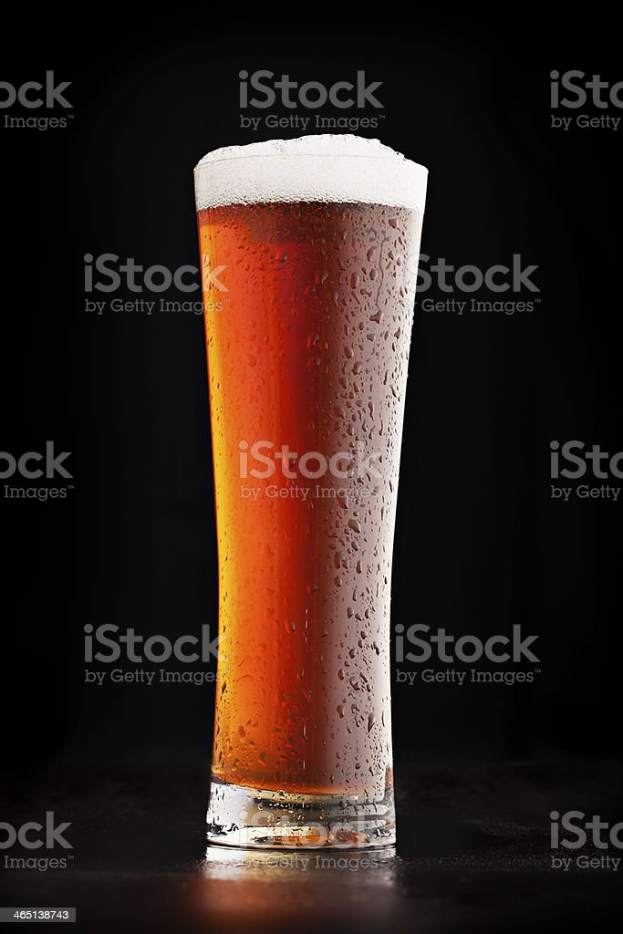 Glass of cold amber beer on a dark background stock photo