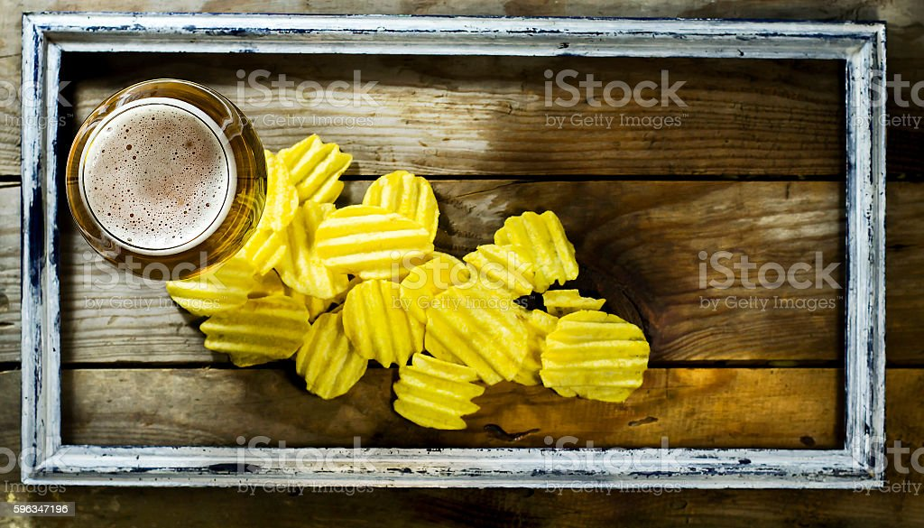 Glass of cold beer and chips in the old frame. royalty-free stock photo