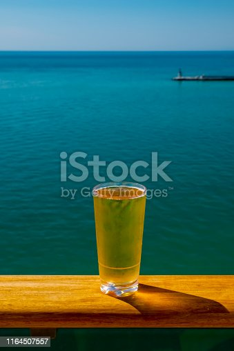 A glass of cold beer on a cruise ship rail.