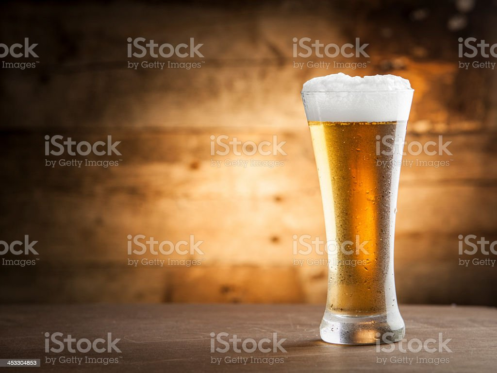 Glass of cold beer with foam on table stock photo