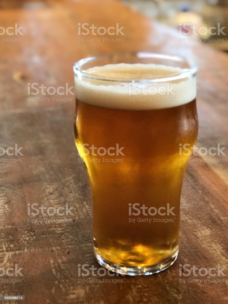 Glass of cold draft beer on a wooden balcony stock photo