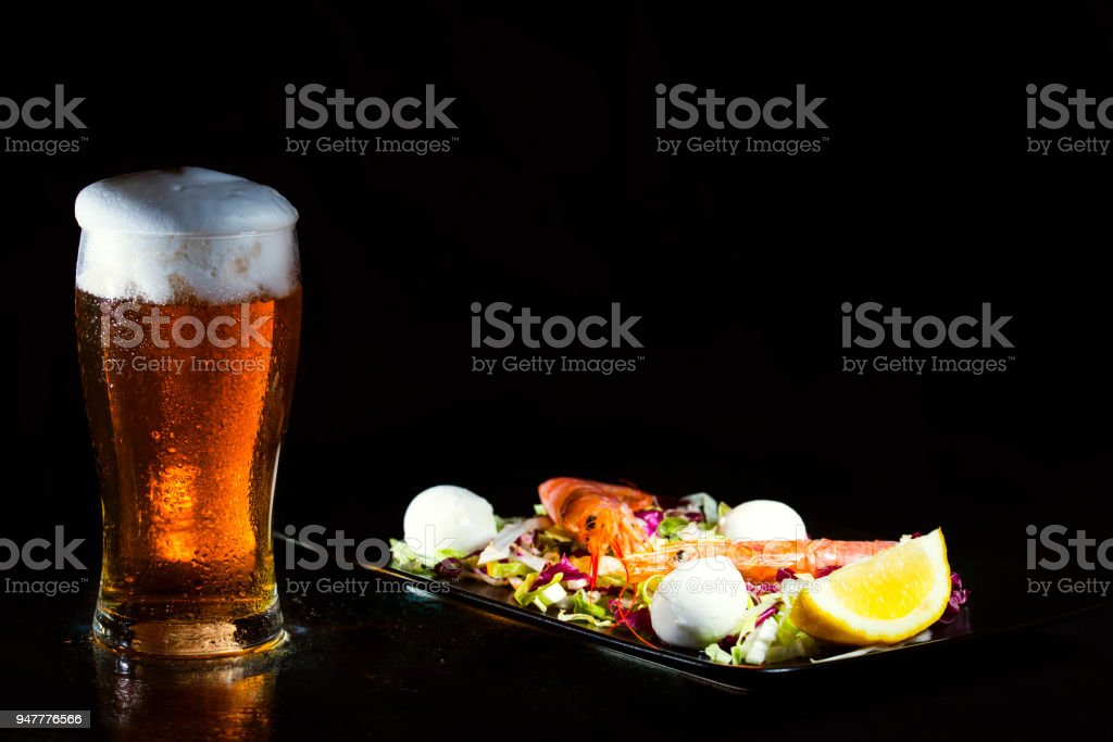 Glass of cold light beer and salad with argentine red shtimp stock photo