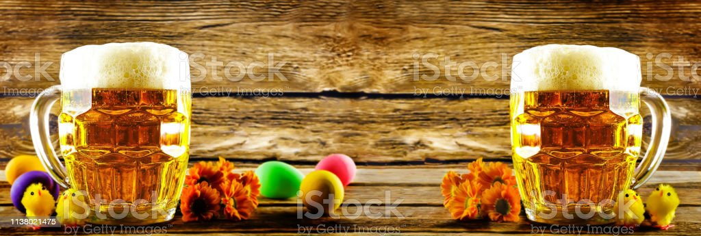 Glass of cold light beer with Easter decorations on a wood background...