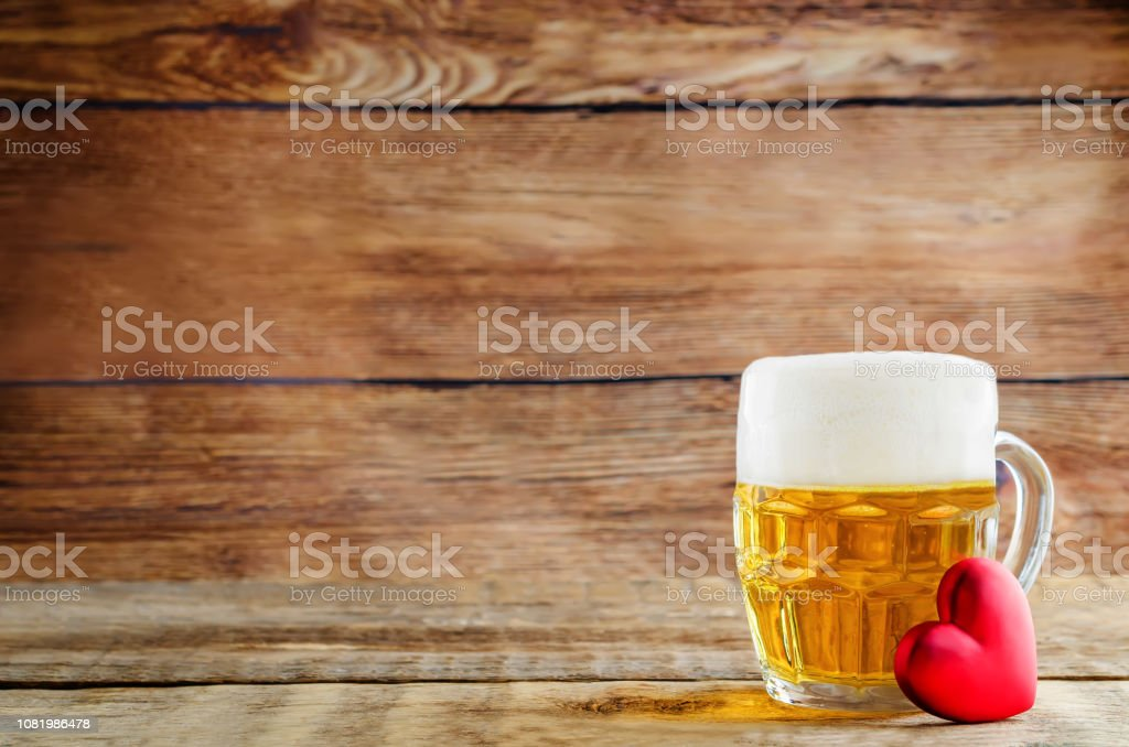 Glass of cold light beer with heart on a wood background for...