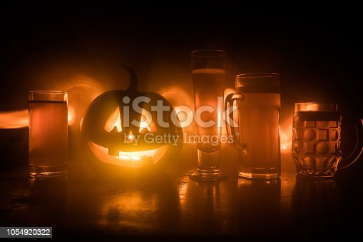 istock Glass of cold light beer with pumpkin on a wood background for Halloween. Glass of fresh beer and pumpkin on a dark toned foggy background 1054920322
