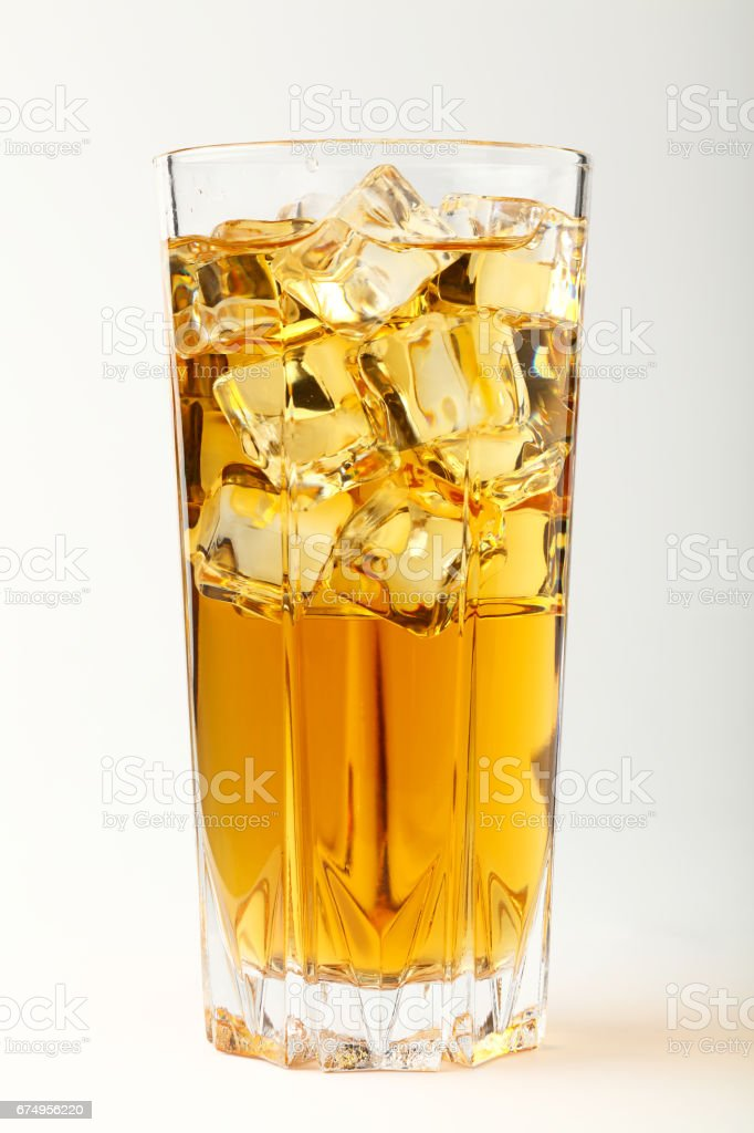 Glass of cold tea with ice cubes over white stock photo
