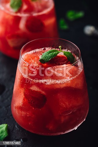 Glass of cool watermelon and strawberry cocktail with fresh mint leaves on dark concrete background