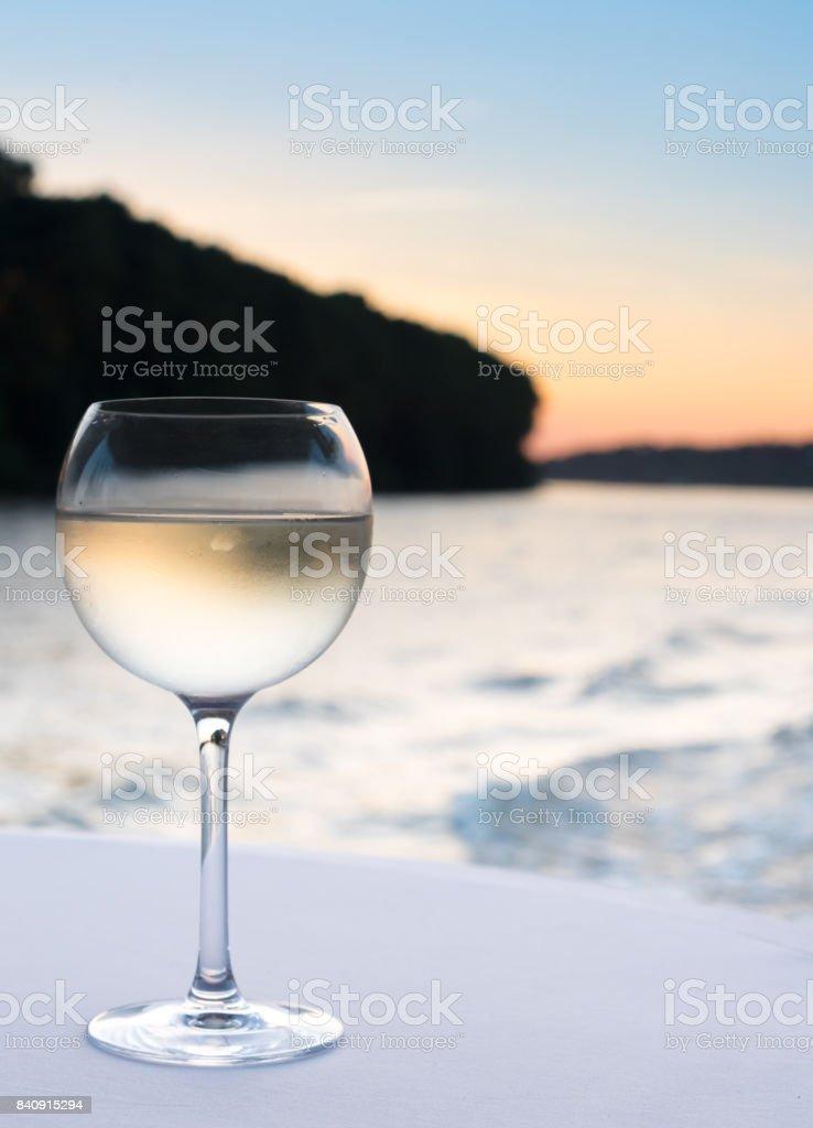 Glas kühlen Weißwein auf weiße Tischdecke mit Küste in unscharfen Hintergrund bei Sonnenuntergang – Foto