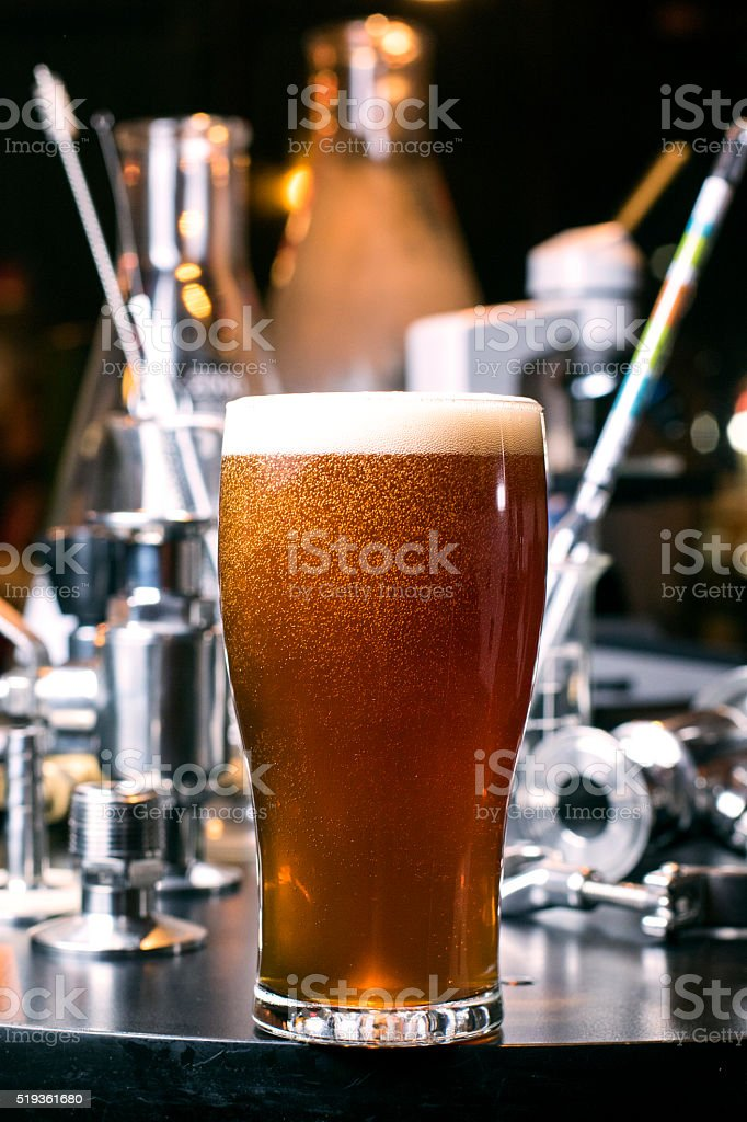 Glass of Craft beer with brewing supplies stock photo
