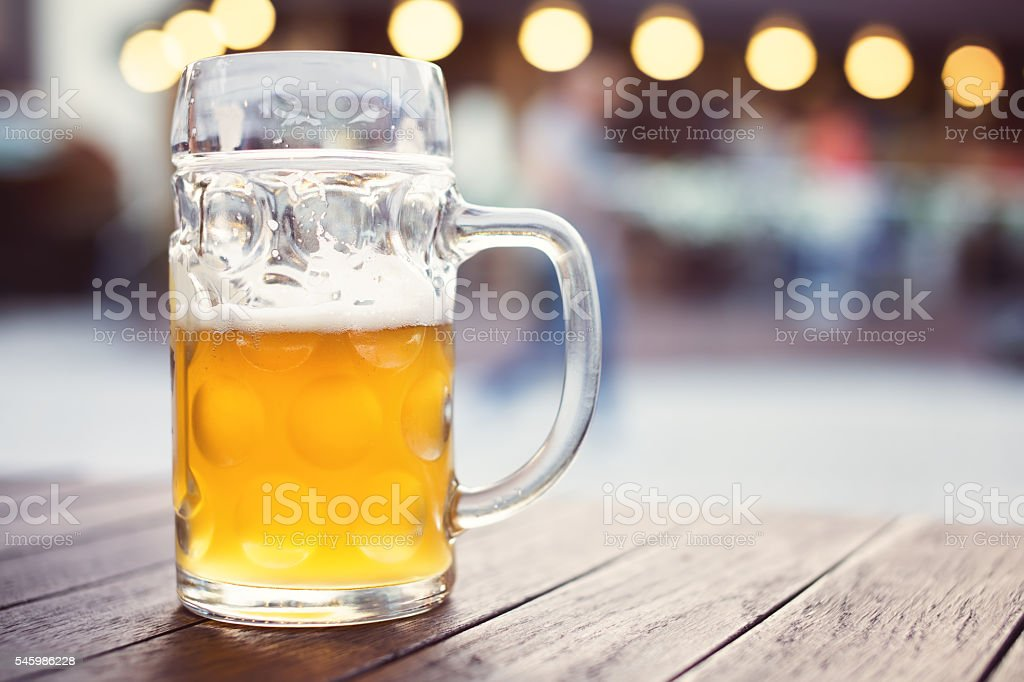 Glass of craft lager beer on pub table. Tapped beer stock photo