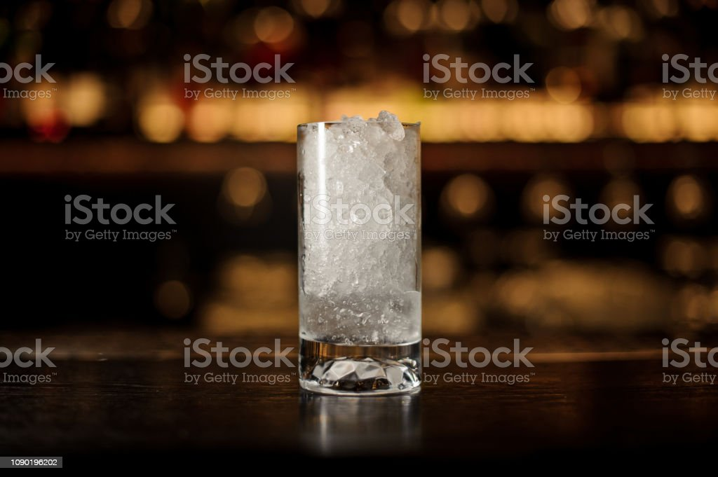 Glass of crushed ice standing on the empty steel bar counter on the...