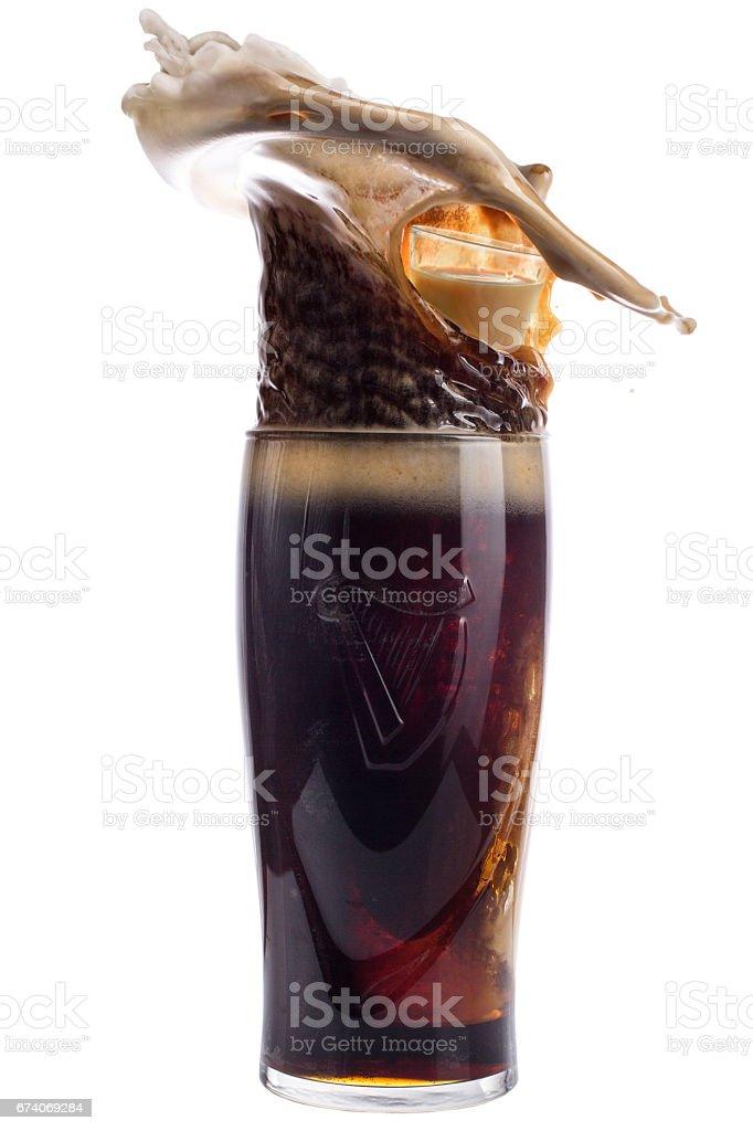 Glass of dark beer on a white background, splash royalty-free stock photo