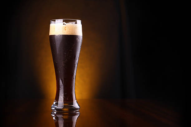 Glass of dark beer Tall glass of dark beer over a dark background lit yellow bitter ale stock pictures, royalty-free photos & images