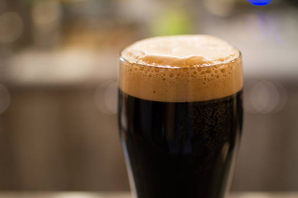 Glass of dark beer Glass - pint- of dark beer with foam bitter ale stock pictures, royalty-free photos & images