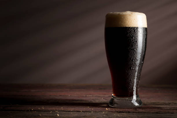 Glass of dark beer Wet glass of cold dark beer with foam placed on a rustic wooden table. lager stock pictures, royalty-free photos & images