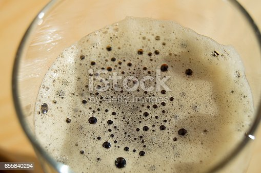 istock Glass of dark beer with foam on wooden background, top View 655840294