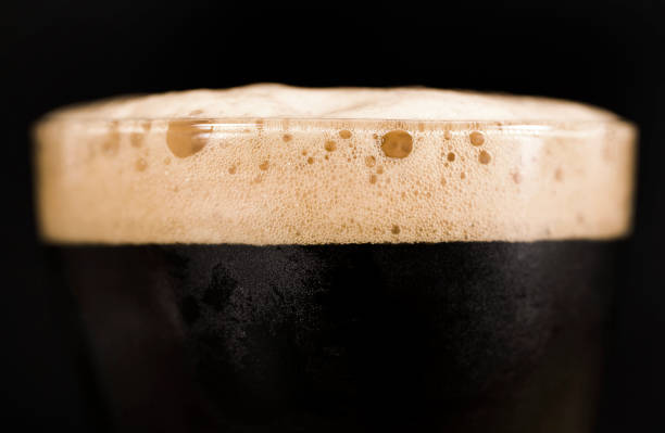 Glass of dark beer with foam Glass of dark beer isolated on black background. Foam close up. bitter ale stock pictures, royalty-free photos & images