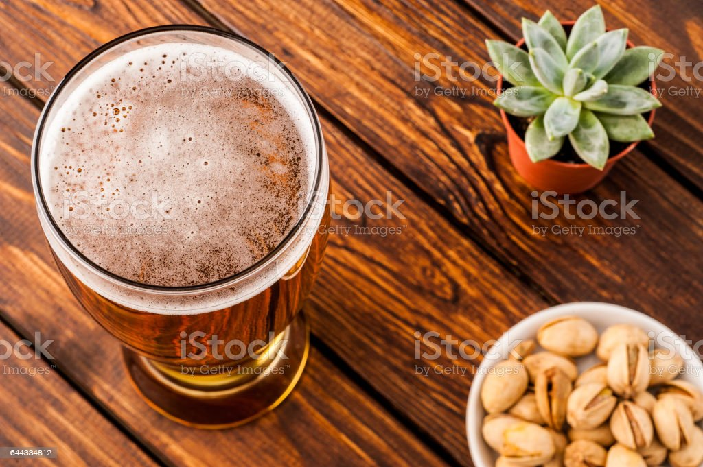 glass of dark cold frothy beer, nuts old wooden table stock photo