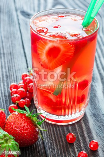 istock Glass of drink with strawberry and red currant on wooden. 479883822
