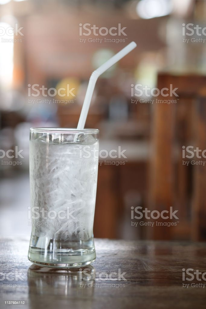 Glass of drinking ice water with ice cube. Ice water drinking concept.